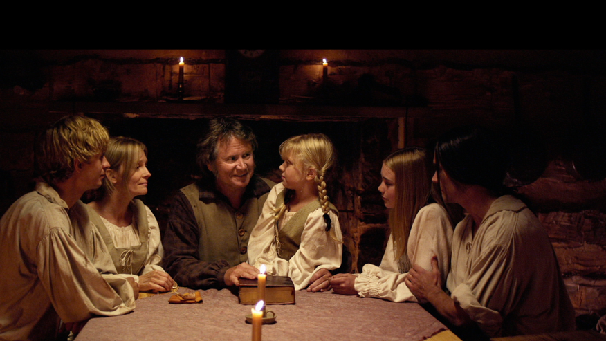 "Papa Leininger (Robert Pierce) reads the Bible aloud to his family in a scene from ""Alone Yet Not Alone."""