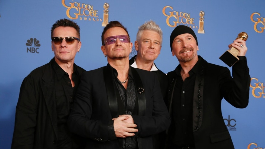 "January 12, 2014. Adam Clayton, Bono, Larry Mullen, Jr., and The Edge (L to R), from the band U2, pose backstage with their award for Best Original Song for ""Ordinary Love"" from the film ""Mandela: Long Walk to Freedom"" at the 71st annual Golden Globe Awards in Beverly Hills, California."