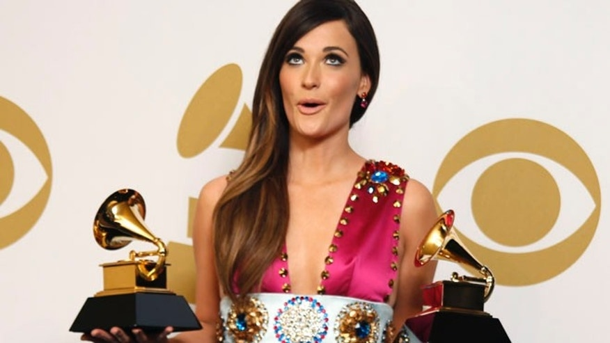 "Country singer Kacey Musgraves poses backstage with her awards for Best Country Song for ""Merry Go 'Round"" and Best Country Album for ""Same Trailer Different Park"" at the 56th annual Grammy Awards in Los Angeles, California January 26, 2014.    REUTERS/Lucy Nicholson (UNITED STATES  TAGS:ENTERTAINMENT) (GRAMMYS-BACKSTAGE) - RTX17WHH"