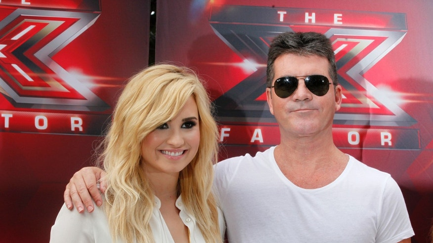 "July 11. 2013. Singer Demi Lovato (L) and producer Simon Cowell, judges for the upcoming season of the Fox television network reality series ""The X Factor"", pose during a photo opportunity in Los Angeles."