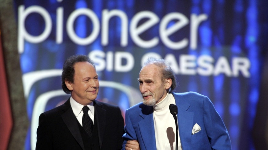 Legendary comedian Sid Caesar accepts the TV Land Pioneer award presented by friend and comedian Billy Crystal (L) during a taping of the TV Land awards show in Santa Monica, California, March 19, 2006. The awards show, which honors classic television performers and their shows, will be telecast on the TV Land cable channel March 22. REUTERS/Fred Prouser - RTR17EYM