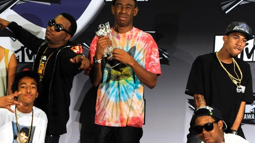 In this Aug. 28, 2011 file photo, Tyler, The Creator, center, holds the award for best new artist as he poses with other members of Odd Future at the MTV Video Music Awards in Los Angeles. New Zealand immigration authorities have banned the Los Angeles rappers from entering the country.