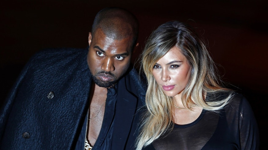 September 29, 2013. Kanye West (L) and companion Kim Kardashian arrive at the Givenchy Spring/Summer 2014 women's ready-to-wear fashion show during Paris Fashion Week.