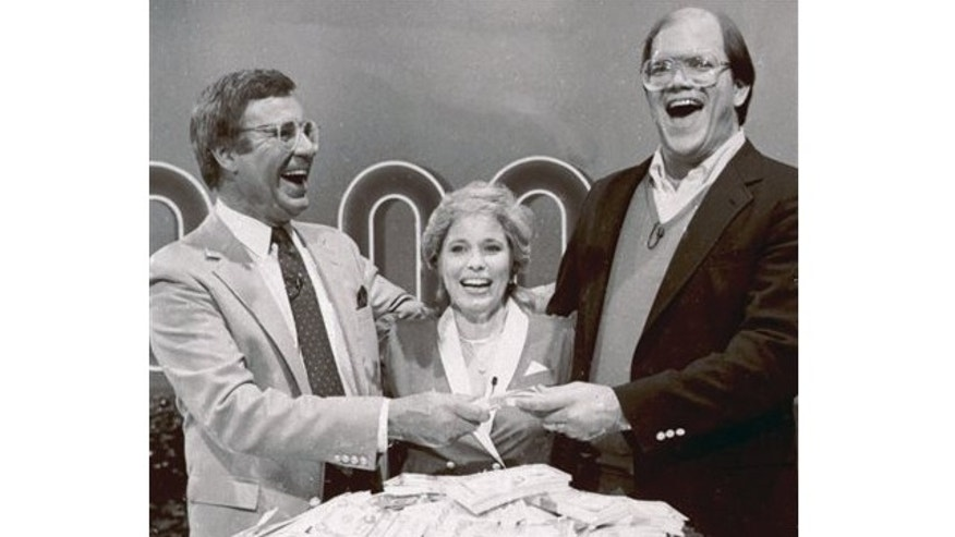 "FILE: Jan. 16, 1986: Host Jim Lange, left, congratulating Connie and Steve Rutenbar of Mission Viejo, Calif., after they won $1 million on the TV show, ""The $1,000,000 Chance of a Lifetime""."