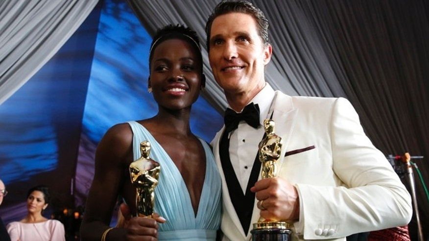 Matthew McConaughey and Lupita Nyong'o hold their Oscars for Best Actor and Best Supporting Actress respectively at the Governors Ball after the 86th Academy Awards in Hollywood, California March 2, 2014.  REUTERS/Adrees Latif (UNITED STATES  - Tags: ENTERTAINMENT)   (OSCARS-PARTIES) - RTR3FYQM