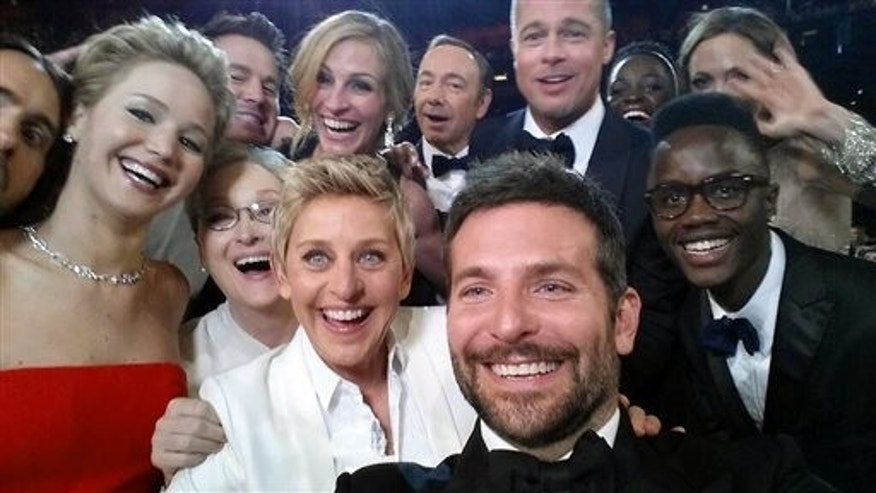 "This image released by Ellen DeGeneres shows actors front row from left, Jared Leto, Jennifer Lawrence, Meryl Streep, Ellen DeGeneres, Bradley Cooper, Peter Nyongo Jr., and, second row, from left, Channing Tatum, Julia Roberts, Kevin Spacey, Brad Pitt, Lupita Nyongo and Angelina Jolie as they pose for a ""selfie"" portrait on a cell phone during the Oscars at the Dolby Theatre on Sunday, March 2, 2014, in Los Angeles. (AP Photo/Ellen DeGeneres)"
