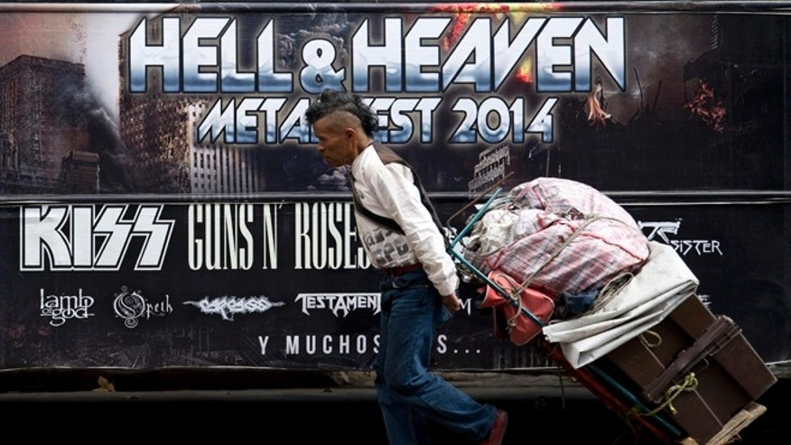 "A man pulls a dolly loaded with supplies past publicity of  ""Hell and Heaven Metal Fest"" concert, posted on bus in Mexico City, Friday March 7, 2014. The Mexico state government canceled the concert saying the March 15-16 ""Hell and Heaven Metal Fest"" planned for a fairground just east of Mexico City did not have adequate safety plans, posing a risk to concert-goers. (AP Photo/Eduardo Verdugo)"