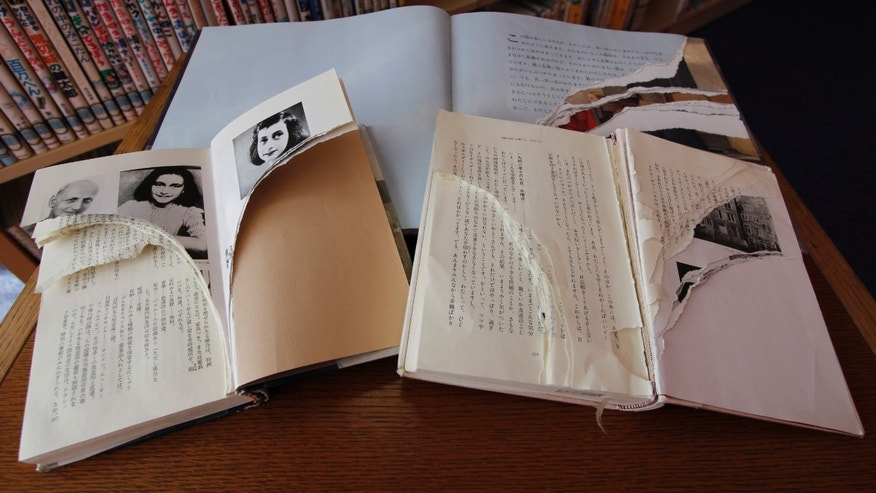 "Feb. 21, 2014 photo, ripped copies of Anne Frank's ""Diary of a Young Girl"" and related books are shown at Shinjuku City Library in Tokyo. Japanese police have arrested a man for allegedly tearing pages out of books related to Frank at a Tokyo library."