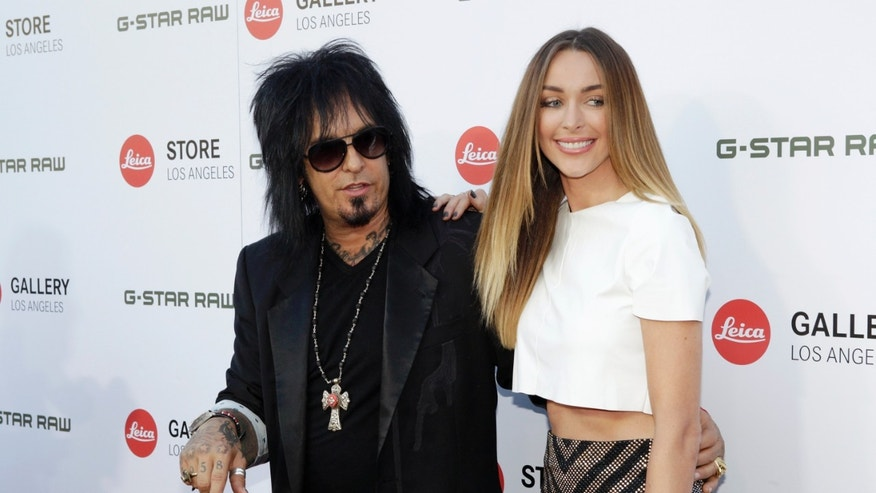 June 20, 2013. Musician Nikki Sixx and Courtney Bingham pose at the launch of the Leica Store Los Angeles in Los Angeles.