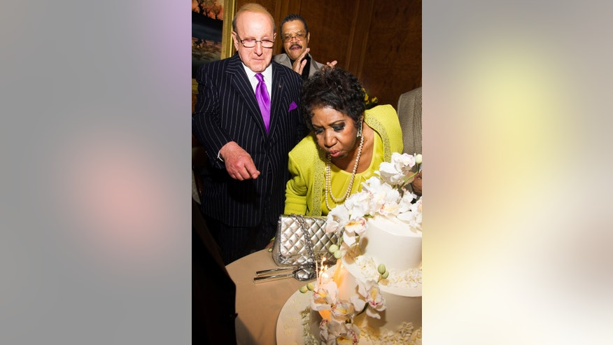 March 23, 2014. Clive Davis helps Aretha Franklin blow out candles on her cake at her 72nd birthday celebration in New York.