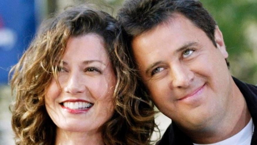 "Country music singer Amy Grant (L) and her husband Vince Gill posebetween songs during an appearance on NBC television's ""Today Show"" inNew York on July 12, 2002. Gill and Grant appeared as part of theshow's ""Summer Concert Series."" REUTERS/Peter MorganMMR - RTR7KCM"