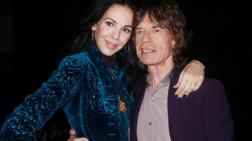 Musician Mick Jagger and designer L'Wren Scott pose following her Fall/Winter 2012 collection during New York Fashion Week, February 16, 2012.     REUTERS/Carlo Allegri (UNITED STATES - Tags: FASHION ENTERTAINMENT) - RTR2XZOE