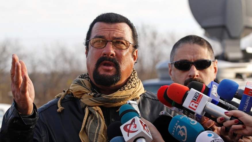 U.S. actor Steven Seagal talks to the media after he adopted Grivei, a stray dog from the Dogtown kennel in Uzunu, 40 km (24 miles) south of Bucharest November 17, 2013.