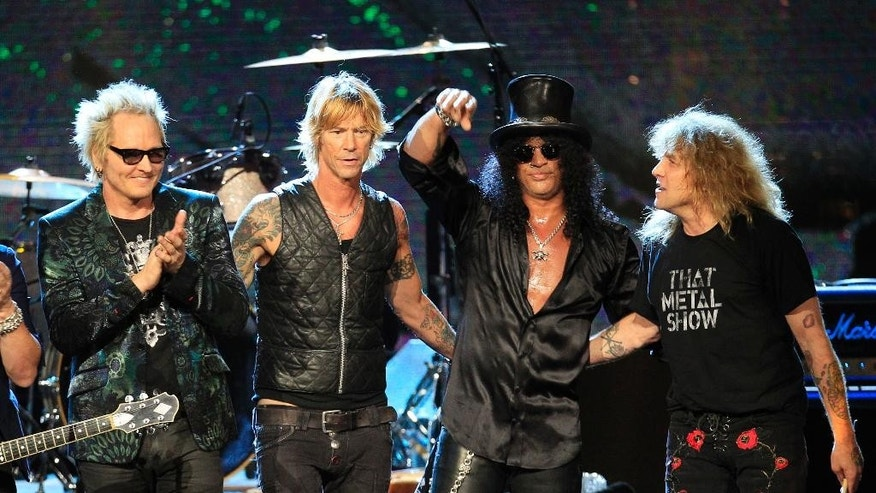 "FILE - This April 15, 2012 file photo shows Guns N' Roses, from left, Matt Sorum, Duff McKagan, Slash and Steven Adler, after their performance following induction into the Rock and Roll Hall of Fame, in Cleveland. Frontman Axl Rose decided to skip the ceremony because it didn't ""appear to be somewhere I'm actually wanted or respected."" Guitarist Slash, bassist McKagen and drummer Adler, however, did take the stage, performing together for the first time in nearly two decades. (AP Photo/Tony Dejak, file)"