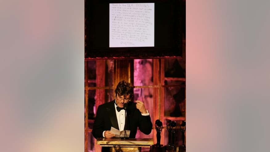 "FILE- In this March 13, 2006 file photo, Jann Wenner, vice chairman of the Rock & Roll Hall of Fame board of directors, reads a letter from the Sex Pistols refusing to attend their own induction into the Rock & Roll Hall of Fame during ceremonies, in New York.  The British band, which featured lead singer Johnny Rotten and late bassist Sid Vicious, said in a hand-written note posted on its website that the hall was like ""urine in wine"" selling ""old famous"": ""Were not coming. Were not your monkeys and so what?"" (AP Photo/Jeff Christensen, file)"