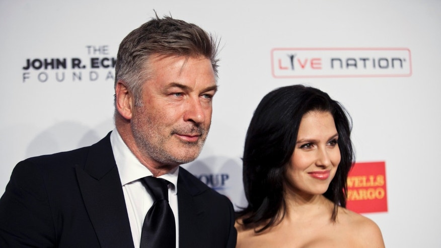 """Actor Alec Baldwin, left, and his wife Hilaria Baldwin arrive at the Elton John AIDS Foundation's 12th Annual """"An Enduring Vision"""" benefit gala at Cipriani in New York October 15, 2013."""