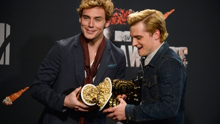 April 13, 2014: Sam Claflin, left, poses with the award for best movie of the year and Josh Hutcherson poses with the award for best male performance for 'The Hunger Games: Catching Fire' in the press room at the MTV Movie Awards at Nokia Theatre in Los Angeles. (Photo by Jordan Strauss/Invision/AP)