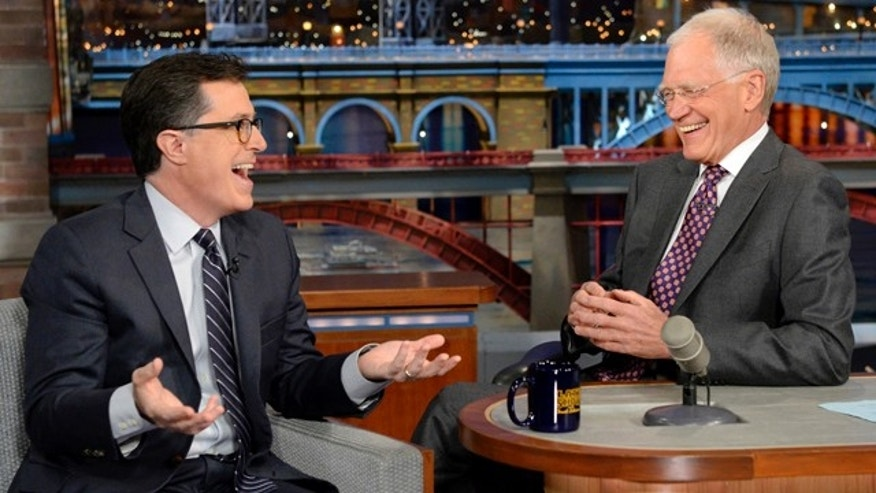 April 22, 2014: In this photo provided by CBS, Comedy Central's Stephen Colbert, left, joins host David Letterman on the set of 'The Late Show with David Letterman.' This was Colbert's first visit to the show since CBS announced that he will succeed Letterman as host when he retires in 2015. (AP Photo/Jeffrey R. Staab)