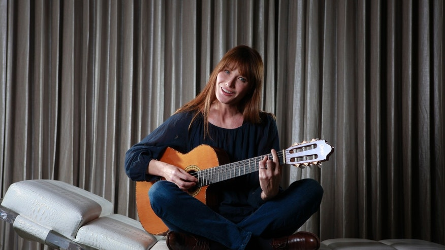 "June 25, 2013. Singer Carla Bruni-Sarkozy sings as she poses for a portrait to promote her new album ""Little French Songs"" in New York."
