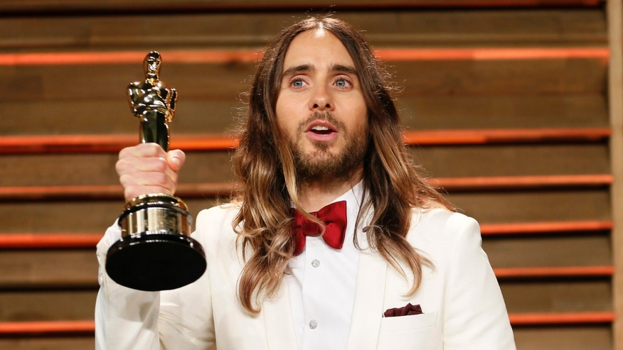 March 2, 2014. Actor Jared Leto holds his award for best supporting actor as he arrives at the 2014 Vanity Fair Oscars Party in West Hollywood, California.