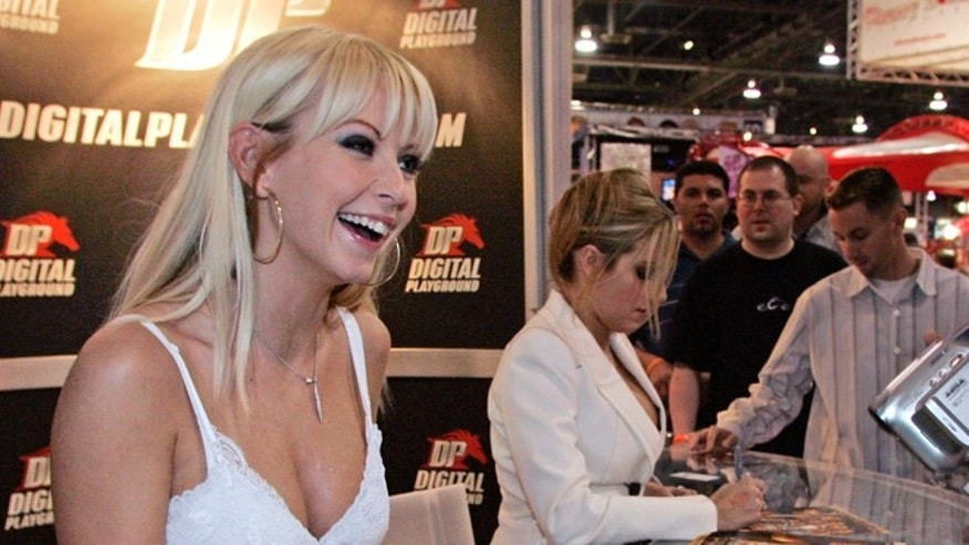 Adult film actress Jana Cova talks with a fan in the Digital Playground booth during the AVN Adult Entertainment Expo in Las Vegas, Nevada January 6, 2006. Actress Teagan Presley signs autographs in the background. Presley said her Chase bank account was closed.