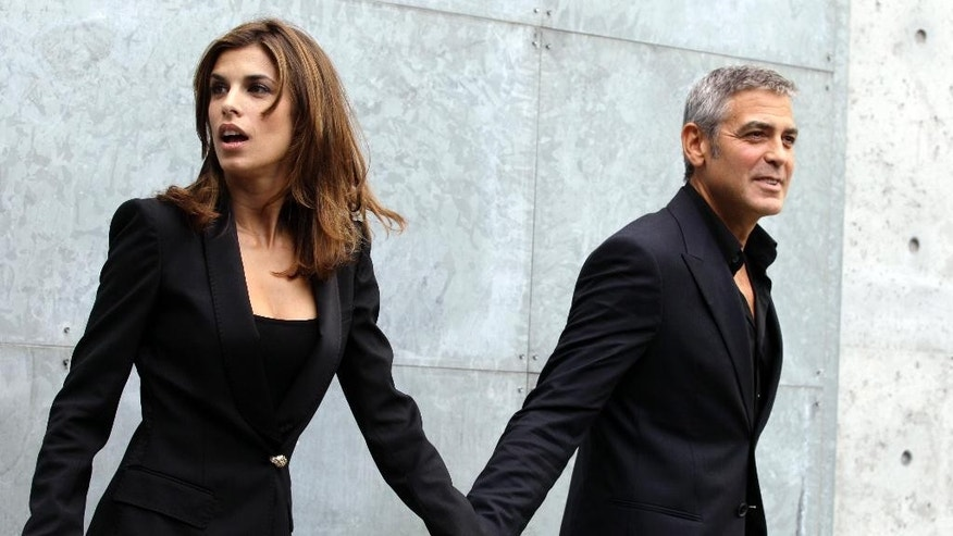 FILE - In this Sept. 27, 2010 file photo, American actor George Clooney holds hands with his girlfriend Elisabetta Canalis prior to the presentation of the Armani Spring-Summer 2011 fashion collection, during the fashion week in Milan, Italy. Clooney, 52, Hollywood's most determined bachelor famous for a litany of fleeting loves, has taken himself off the romantic market and proposed to 36-year-old attorney, Amal Alamuddin. A spokesman for the Oscar-winning actor and producer did not respond to requests for comment Monday, April 28, 2014.  (AP Photo/Luca Bruno, file)