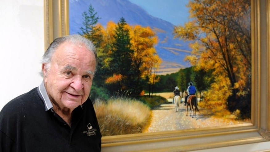 This June 2012 photo shows former Mad magazine editor Al Feldstein standing near one of his paintings at Livingston HealthCare.