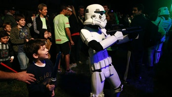 A boy looks at a man dressed as a stormtrooper from the Star Wars movies before the Star Wars Run race ahead of Star Wars Day in Buenos Aires May 3, 2014.   REUTERS/Marcos Brindicci (ARGENTINA - Tags: SOCIETY) - RTR3NPB9
