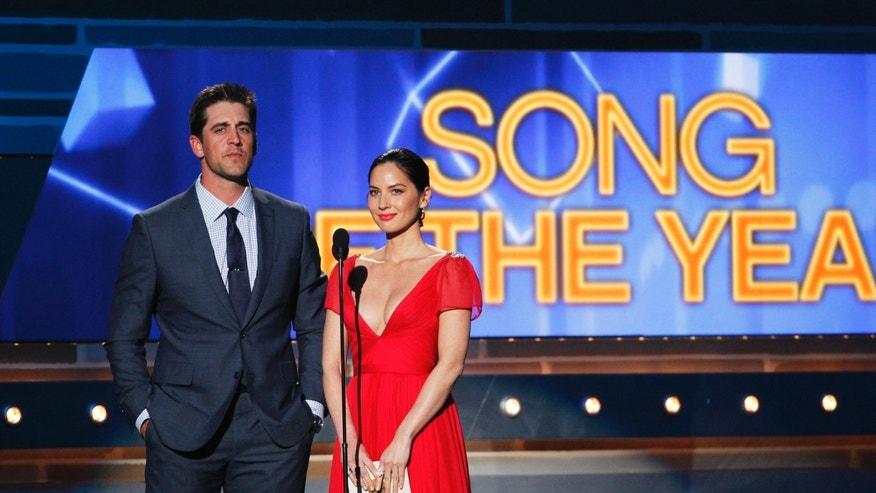 April 6, 2014. NFL football player Aaron Rogers and actress Olivia Munn present the Song of the Year Award on stage at the 49th Annual Academy of Country Music Awards in Las Vegas, Nevada.