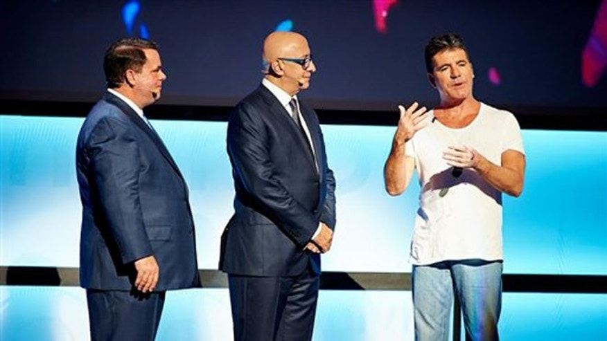 Univision executives Steve Mandala and Alberto Ciurana with Simon Cowell on Tuesday, May 13, 2014 in New York City.