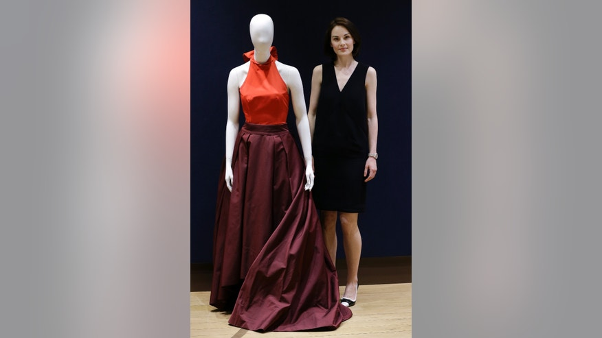 "May 14, 2014. British actress Michelle Dockery, stands with her Prada gown that she wore to the 2013 Emmys at Christie's auction rooms in London.""Downton Abbey"" star Michelle Dockery is selling the eye-catching gown she wore to last year's Emmy Awards to help victims of the Syria civil war."