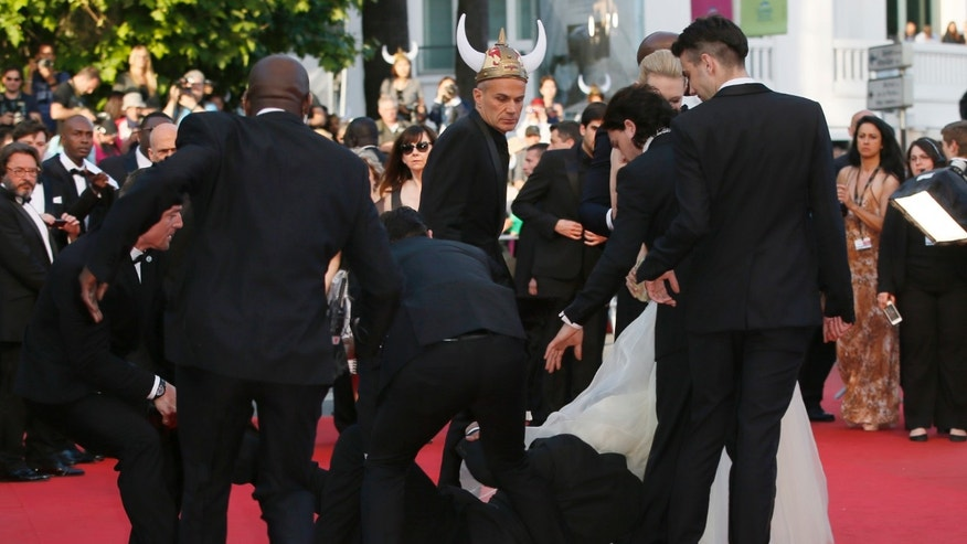 Security run toward a man who ran unauthorized onto the red carpet in Cannes, France, Friday, May 16, 2014.