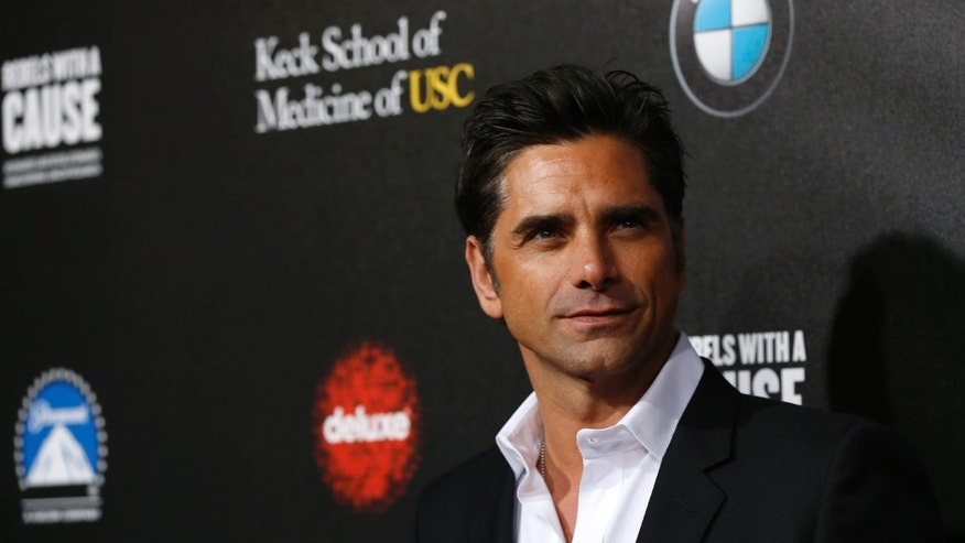 "March 20, 2014. Actor John Stamos poses at the second annual ""Rebels With a Cause"" gala at Paramount Pictures Studios in Los Angeles."
