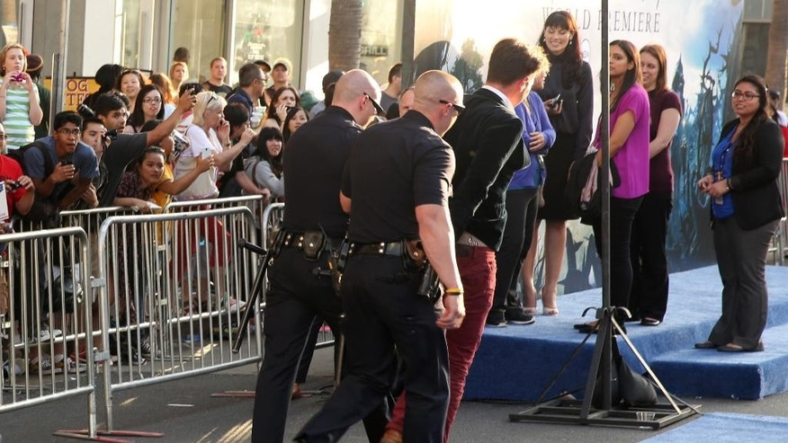 "Journalist Vitalii Sediuk is walked off carpet in handcuffs after allegedly attacking Brad Pitt at the world premiere of ""Maleficent"" at the El Capitan Theatre on Wednesday, May 28, 2014, in Los Angeles. Sediuk's antics have left him with fewer friends in the entertainment world after his publicist and television station cut ties with him over pranks that have once again landed the 25-year-old in handcuffs. He's kissed Will Smith in Moscow, tried to steal Adele's spotlight at the Grammys, dove under America Ferrera's dress at Cannes and now accosted Pitt on the red carpet of a Hollywood premiere. (Photo by Matt Sayles/Invision/AP)"