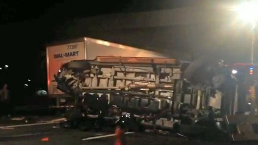 In this image from video the limousine bus carrying Tracy Morgan and six other people lies on it's side early Saturday morning June 7, 2014 on the New Jersey Turnpike. Morgan remained hospitalized as state and federal officials continued their investigation of the six-vehicle crash on the New Jersey Turnpike that took the life of a Morgan friend and left two others seriously injured, authorities say. (AP Photo/Will Vaultz Photography)