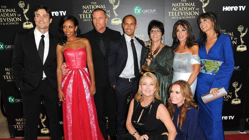 "The cast and crew of ""The Young and the Restless"" poses in the press room with the award for outstanding drama series at the 41st annual Daytime Emmy Awards at the Beverly Hilton Hotel on Sunday, June 22, 2014, in Beverly Hills, Calif. (Photo by Richard Shotwell/Invision/AP)"