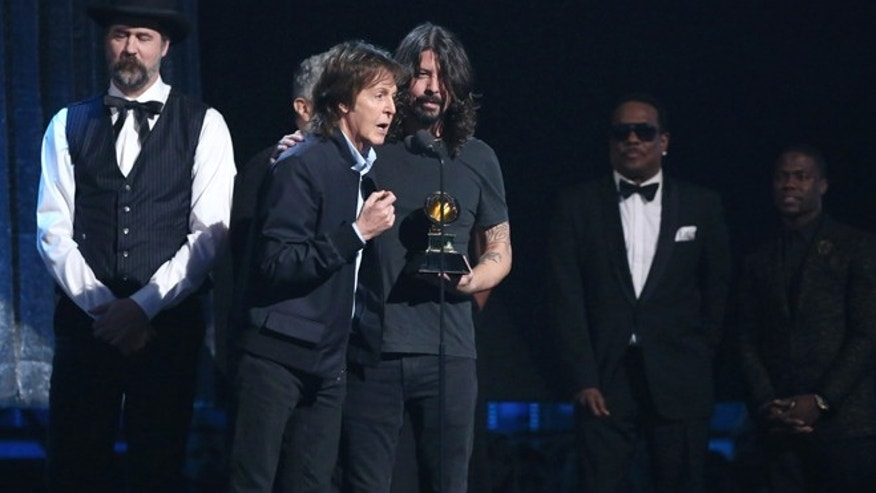 Krist Novoselic, left, looks on as Paul McCartney, center left, and Dave Grohl, center right, accept the award for best rock song for Cut Me Some Slack at the 56th annual Grammy Awards at Staples Center on Sunday, Jan. 26, 2014, in Los Angeles. (Photo by Matt Sayles/Invision/AP)