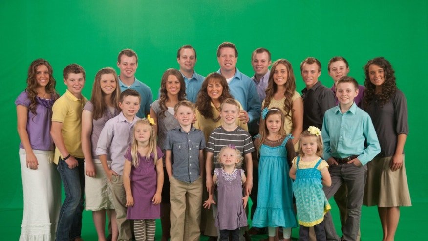 The Duggar family in front of a green screen.