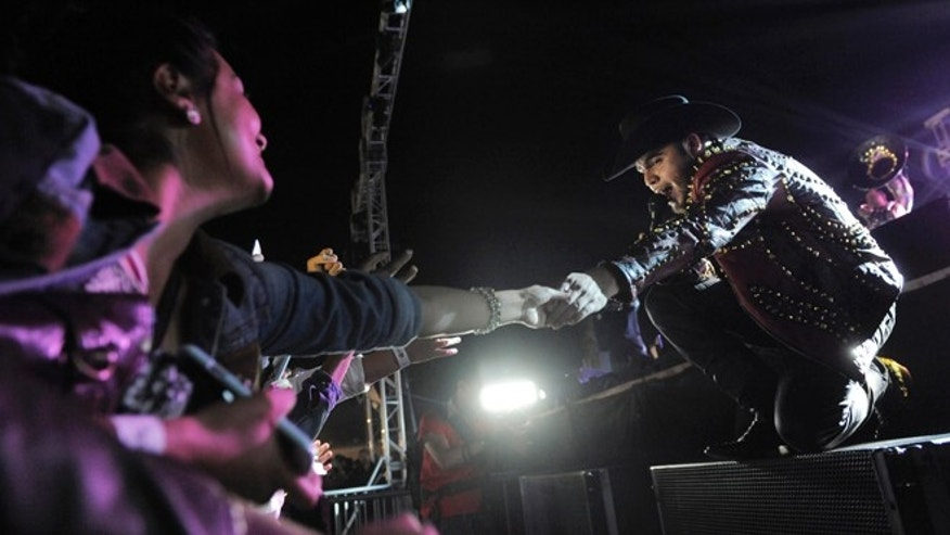 In this June 13, 2014 photo, Gerardo Ortiz joins hands with a fan during a concert at the Ventura County in Ventura, Calif.