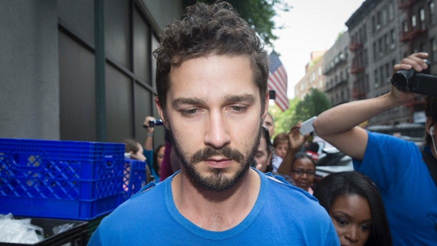 "June 27, 2014. Actor Shia LaBeouf is followed by media after leaving Midtown Community Court following his arrest the previous day for yelling obscenities at the Broadway show ""Cabaret."""