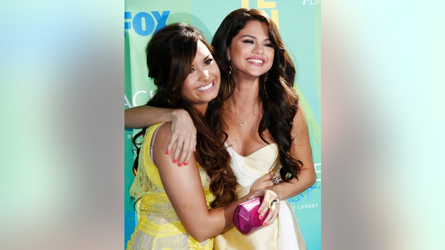 August 7, 2011. Singer Demi Lovato (L) and actress Selena Gomez pose together as they arrive at the Teen Choice Awards in Los Angeles.