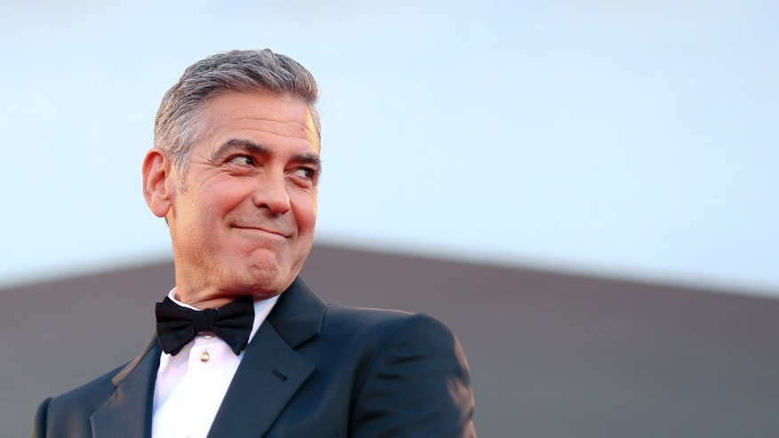 "August 28, 2013. George Clooney smiles as he arrives on the red carpet for the premiere of ""Gravity"" at the 70th Venice Film Festival in Venice."