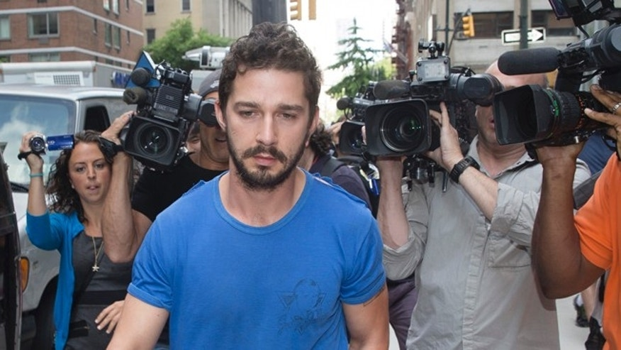"""June 27, 2014. Actor Shia LaBeouf walks through the media in New York, after leaving Midtown Community Court following his arrest the previous day for yelling obscenities at the Broadway show """"Cabaret."""""""