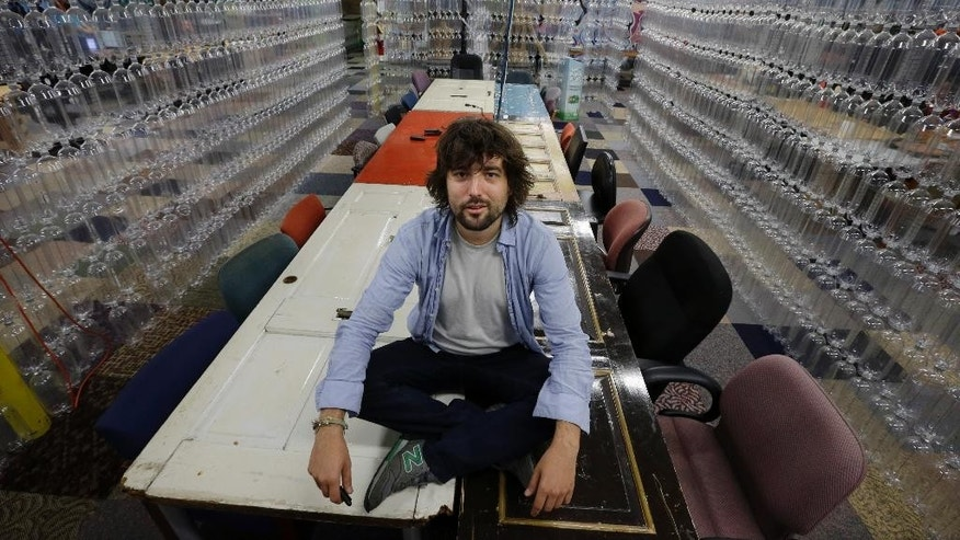 "TerraCycle Inc. founder Tom Szaky sits on a table made from old doors in a meeting room with walls of recycled soda bottles at the company Tuesday, Aug. 5, 2014, in Trenton, N.J. Founded in 2001 by then-20-year-old Princeton student Szaky, TerraCycle works to collect and transform a range of hard-to-recyle items, from potato chip bags to cigarette butts, into colorful consumer products. A new reality show launching Aug. 8 will focus on the New Jersey-based recycling company. The reality docu-drama called ""Human Resources,"" chronicles what it's like to work at the Trenton-based company. (AP Photo/Mel Evans)"