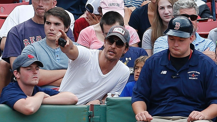Actor Matthew McConaughey, center, watches the baseball game at Fenway Park during the eighth inning between the Boston Red Sox and the Houston Astros in Boston, Sunday, Aug. 17, 2014. (AP Photo/Michael Dwyer)