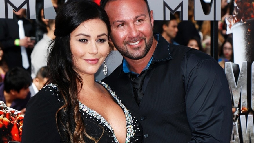 Jennifer Farley, also known as JWoww, poses with her fiance Roger Mathews upon arrival at the 2014 MTV Movie Awards in Los Angeles, California  April 13, 2014.