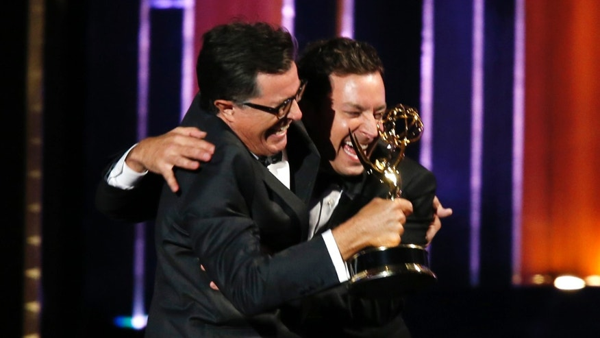 "Stephen Colbert (L) and Jimmy Fallon celebrate after Colbert accepted the award for Outstanding Variety Series for Comedy Central's ""The Colbert Report"" onstage during the 66th Primetime Emmy Awards in Los Angeles, California August 25, 2014.  REUTERS/Mario Anzuoni (UNITED STATES - Tags: Entertainment)(EMMYS-SHOW) - RTR43QQ0"