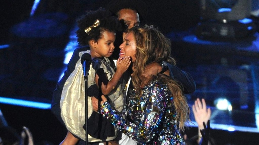 Beyonce on stage hugs Jay Z and their daughter Blue Ivy as she accepts the Video Vanguard Award at the MTV Video Music Awards at The Forum, in Inglewood, Calif.