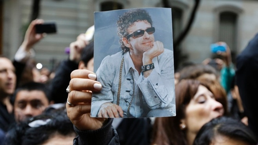 A fan holds a photo of Argentine rock star Gustavo Cerati before the departure of the funeral car transporting Cerati's remains, in Buenos Aires, Argentina, Friday, Sept. 5, 2014. Cerati died on Thursday, four years after a stroke put him in a coma and ended the career of one of Latin America's most influential musicians. (AP Photo/Victor R. Caivano)