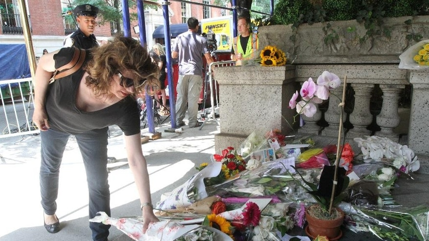 September 5, 2014. Paula Reardon places flowers at a sidewalk memorial for comedian Joan Rivers at the doorstep of her apartment building.